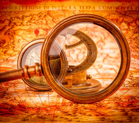Vintage still life. Vintage magnifying glass lies on an ancient world map in 1565. photo