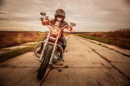 rider: Biker girl in a leather jacket and helmet on a motorcycle