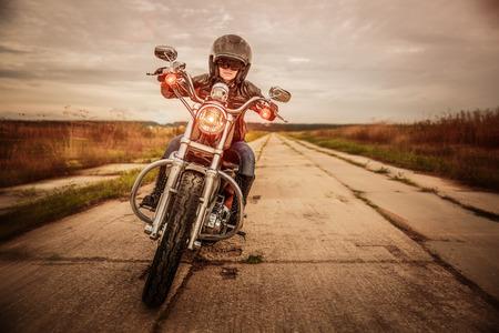 casco moto: Muchacha del motorista en una chaqueta de cuero y el casco en una motocicleta