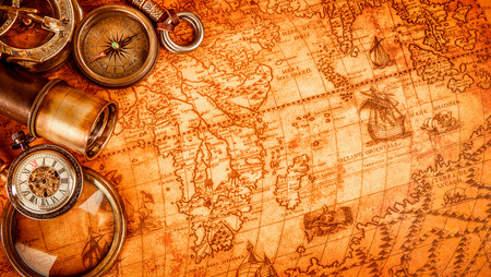 Vintage magnifying glass, compass, telescope and a pocket watch lying on an old map in 1565. Stock Photo
