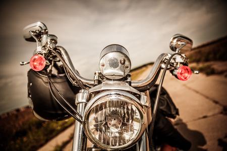 casco moto: Motocicleta en la carretera con un casco en el manillar.