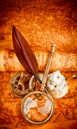 ancient map: Vintage compass, magnifying glass, pocket watch, quill pen, spyglass lie on an old ancient map in 1565 with a lit candle. Vintage still life.