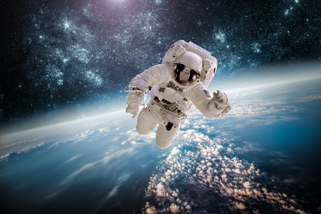 Astronaut in outer space against the backdrop of the planet earth. Elements of this image furnished by NASA. Banco de Imagens