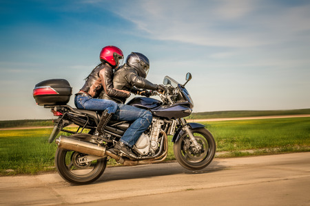 Couple Bikers in a leather jacket riding a motorcycle on the road