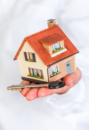 hands holding house: House an key in human hands on a white background