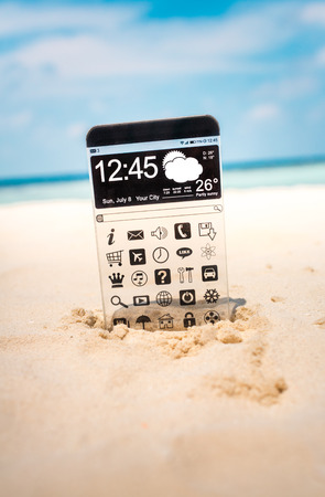 Futuristic Smart phone (phablet) with a transparent display in the sand on the beach. Concept actual future innovative ideas and best technologies humanity. photo
