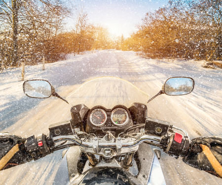 snowmobile: Biker rides on winter slippery road. First-person view.