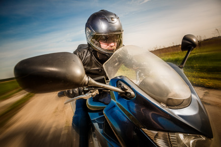 biker: Biker in helmet and leather jacket racing on the road Stock Photo