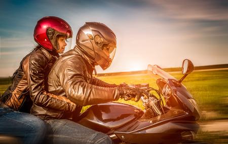 kurtka: Rowerzyści para w skórzanej kurtce jazda motocyklem na drodze Zdjęcie Seryjne