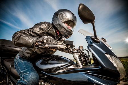 casco moto: Motorista en las carreras de casco y la chaqueta de cuero en el camino