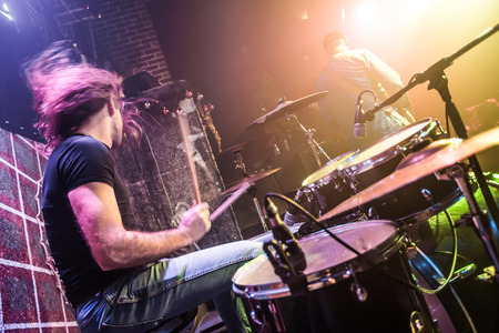 tambor: El baterista de juego en el tambor establece en el escenario. Advertencia - Centrarse en el tambor, tiro auténtico con alta iso en condiciones de iluminación difíciles. Un pequeño grano de bits y efectos de movimiento borrosas.