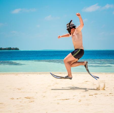 flippers: Hombre divertido que salta en aletas y máscara. Vacaciones de vacaciones en una playa tropical de las Islas Maldivas.