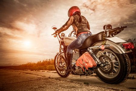 helmet moto: Muchacha del motorista en una chaqueta de cuero y el casco en una motocicleta