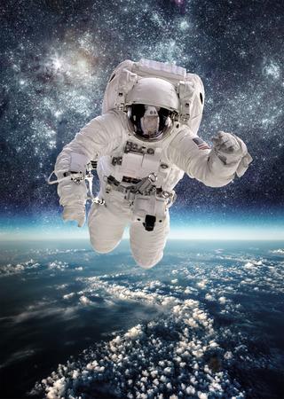cohetes: Astronauta en el espacio exterior contra el tel�n de fondo del planeta tierra. Foto de archivo