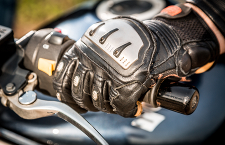 hand brake: Human hand in a Motorcycle Racing Gloves holds a motorcycle throttle control.  Stock Photo