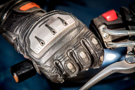 throttle: Human hand in a Motorcycle Racing Gloves holds a motorcycle throttle control.  Stock Photo