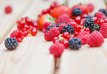 Variety of different berries on a wooden table photo