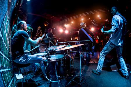 concierto de rock: Banda realiza en etapa, concierto de música rock. Advertencia - tiroteo auténtico con alta iso en condiciones de iluminación difíciles. Un pequeño grano de bits y efectos de movimiento borrosas.