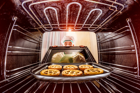 요리사는 오븐에서 파이를 준비하고 오븐 내부에서 봅니다. 오븐에서 요리.