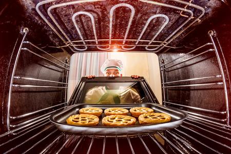 Chef prepara dolci al forno, vista dall'interno del forno. Cottura in forno. Archivio Fotografico - 36583510
