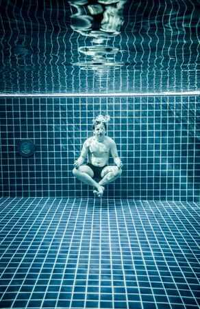 dhyana: Man under water in a swimming pool to relax in the lotus position