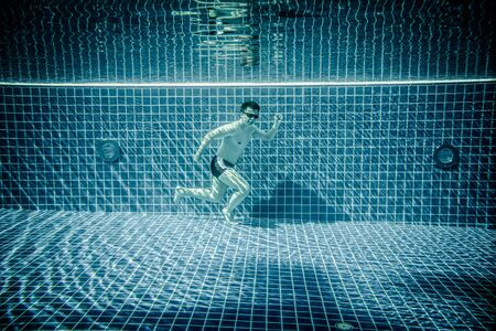 under water: Man under water runs along the bottom of a swimming pool