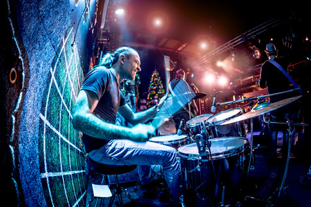 lighting effects: Drummer playing on drum set on stage. Warning - Focus on the drum, authentic shooting with high iso in challenging lighting conditions. A little bit grain and blurred motion effects.