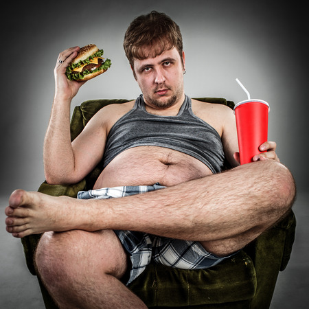 dirty feet: Fat man eating hamburger seated on armchair. Style fast food. Stock Photo