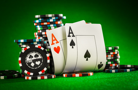 spades: Stack of chips and two aces on the table on the green baize - poker game concept