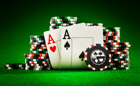 poker: Stack of chips and two aces on the table on the green baize - poker game concept