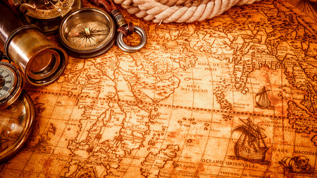 map compass: Vintage magnifying glass, compass, telescope and a pocket watch lying on an old map in 1565. Stock Photo
