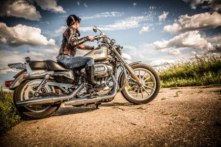 motorrad frau: RUSSLAND-7. Juli 2013: Radfahrerm�dchen und Fahrrad Harley Sportster. Harley Davidson tr�gt eine gro�e Marken-Community, die durch Clubs, Events aktiv h�lt, und ein Museum. Filter in der Postproduktion angewendet.