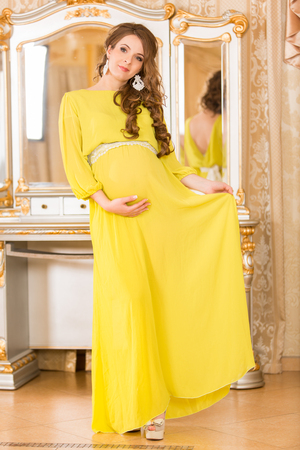 expectant mother: Beautiful pregnant woman in white shirt. Expectant mother. Stock Photo