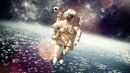 惑星の地球を背景に宇宙の宇宙飛行士。