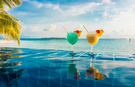 インド洋モルディブの背景には、スイミング プールのそばのカクテル。