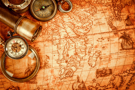 Vintage magnifying glass, compass, telescope and a pocket watch lying on an old map in 1565. Archivio Fotografico