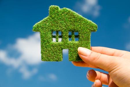 Gras huis op een achtergrond van blauwe hemel in menselijke handen Stockfoto