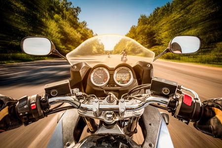 Biker besturen van een motorfiets rijdt langs de asfaltweg. First-person view.