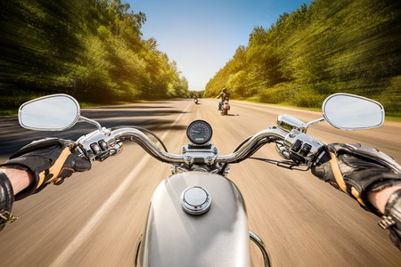 motors: Biker driving a motorcycle rides along the asphalt road. First-person view.