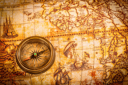 Vintage still life. Vintage compass lies on an ancient world map in 1565. Stockfoto