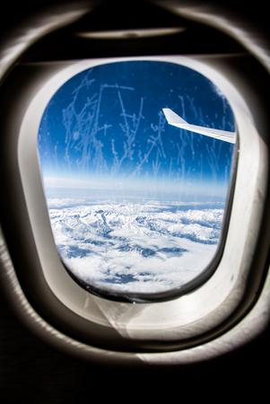 plan éloigné: Image classique à travers la fenêtre de l'avion sur moteur à réaction. Givre sur la fenêtre de verre. Focus sur l'aile de l'avion. Banque d'images