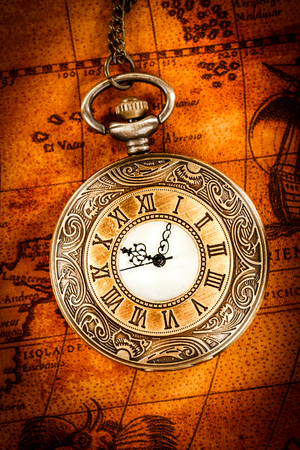 Vintage Antique pocket watch on an ancient world map in 1565.. photo