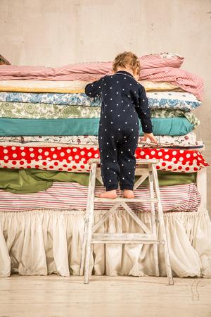 niño escalando: Niño se sube a la cama con un montón de edredones - princesa y el guisante. Foto de archivo