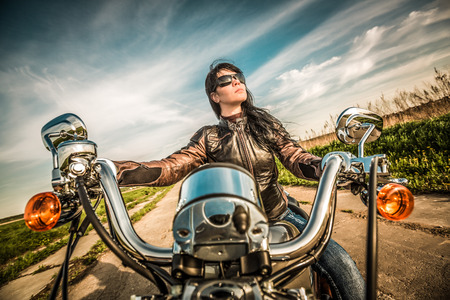 biker girl: Biker girl in a leather jacket on a motorcycle looking at the sunset.