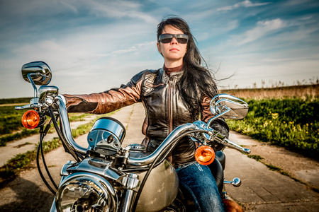 girl bike: Biker girl in a leather jacket on a motorcycle looking at the sunset.