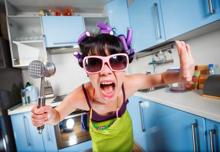 gente loca: Ama de casa loca en un interior de la cocina. Problemas familiares. Foto de archivo