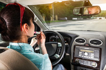 woman from behind: Women make up lips at the wheel the car