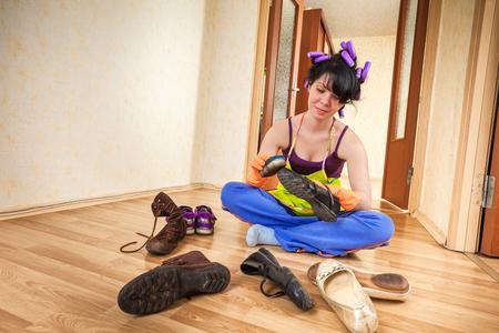 empleada domestica: ama de casa se sienta en un piso y limpia de calzado