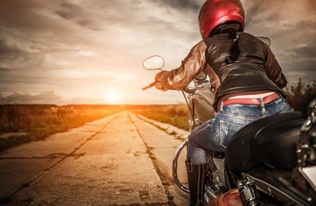 jinete: Muchacha del motorista en una chaqueta de cuero y el casco en una motocicleta. Concéntrese en el tanque de combustible