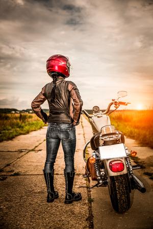 casco de moto: Muchacha del motorista en una chaqueta de cuero y el casco en una motocicleta